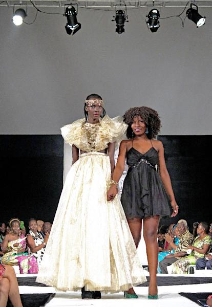 A model (L) presents a creation by designer Martha Jabo during the first fashion week show held in Kampala, on November 15, 2014 (AFP Photo/Amy Fallon)