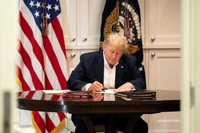 In this handout provided by The White House, President Donald J. Trump works in the Presidential Suite at Walter Reed National Military Medical Center after testing positive for COVID-19 on October 3, 2020 in Bethesda, Maryland. (Photo by Joyce N. Boghosian/The White House via Getty Images)