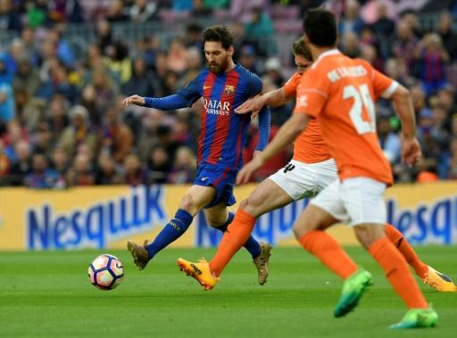 Barcelona's forward Lionel Messi (L) vies with Osasuna's midfielder Roberto Torres during the Spanish league football match April 26, 2017