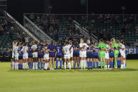 North Carolina Courage and Racing Louisville FC players pause and gather at midfield during the first half of an NWSL soccer match in Cary, N.C., Wednesday, Oct. 6, 2021. (AP Photo/Gerry Broome)