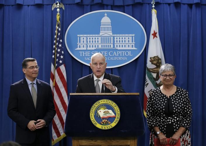 Gov. Jerry Brown, flanked by California Attorney General Xavier Becerra, left, and California Air Resources Board Chair Mary Nichols, discusses a lawsuit filed by 17 states and the District of Columbia over the Trump administration's plans to scrap vehicle emission standards during a news conference Tuesday, May 1, 2018, in Sacramento, Calif. The U.S. Environmental Protection Agency has moved to roll back tailpipe emissions standards for vehicles manufactured between 2022 and 2025. (AP Photo/Rich Pedroncelli)