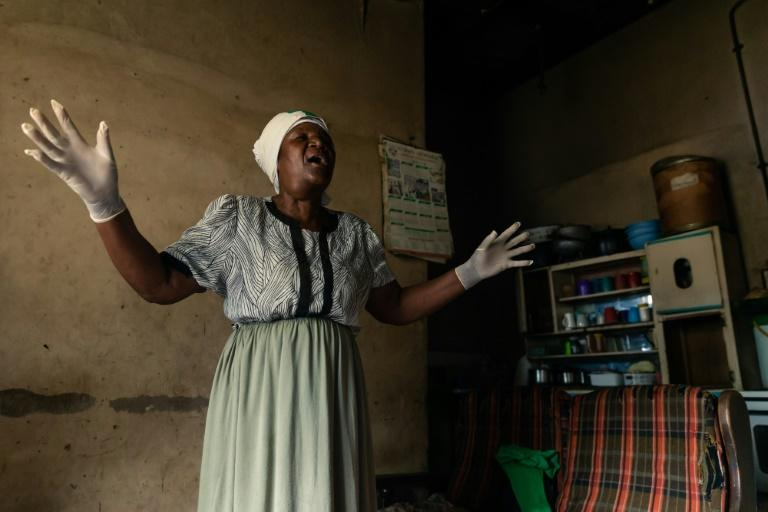 A moment for prayer: Gwena belongs to an Apostolic religious sect where she says she got her calling to take up midwifery. She says she has delivered as many as 250 children (AFP Photo/Jekesai NJIKIZANA)
