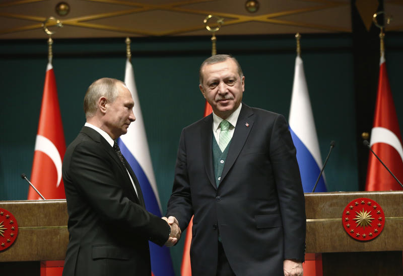 FILE - In this Monday, Dec. 11, 2017 file photo, Turkey's President Recep Tayyip Erdogan, right, shakes hands with Russia's President Vladimir Putin, left, following their joint news statement after their meeting at the Presidential Palace in Ankara, Turkey. NATO-member Turkey has finalized a deal with Moscow to purchase a Russian-made anti-missile system. Under the deal announced by Turkish defense officials on Friday, Dec. 29, 2017. Turkey would buy at least one S-400 surface-to-air missile battery with the option of procuring a second battery. The deal would make Turkey the first NATO member to own Russia's most advanced air defense system and, comes amid Ankara's deteriorating relations with the United States and other western countries. (AP Photo/Burhan Ozbilici, File)