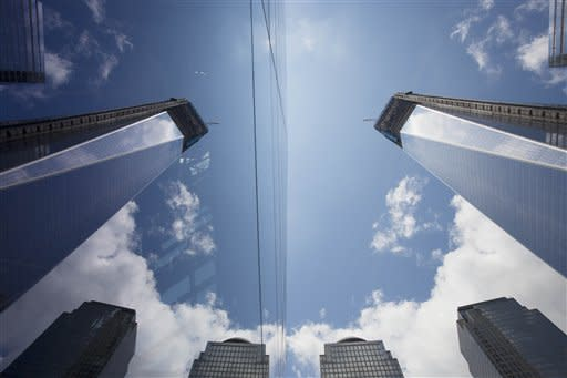 One World Trade Center, right, is reflected in the glass surface of the National September 11 Museum, Thursday, June 14, 2012 in New York. President Barack Obama is scheduled to visit the site later Thursday. (AP Photo/Mark Lennihan)