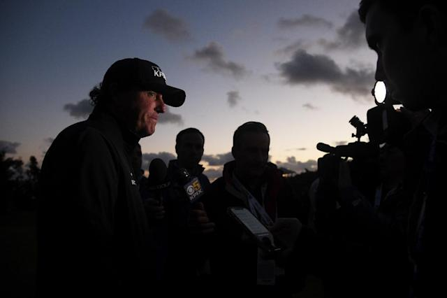 Tournament leader Phil Mickelson is interviewed after darkness halted play in the final round of the Pebble Beach Pro-Am, pushing the finish back to the following day (AFP Photo/Harry How)