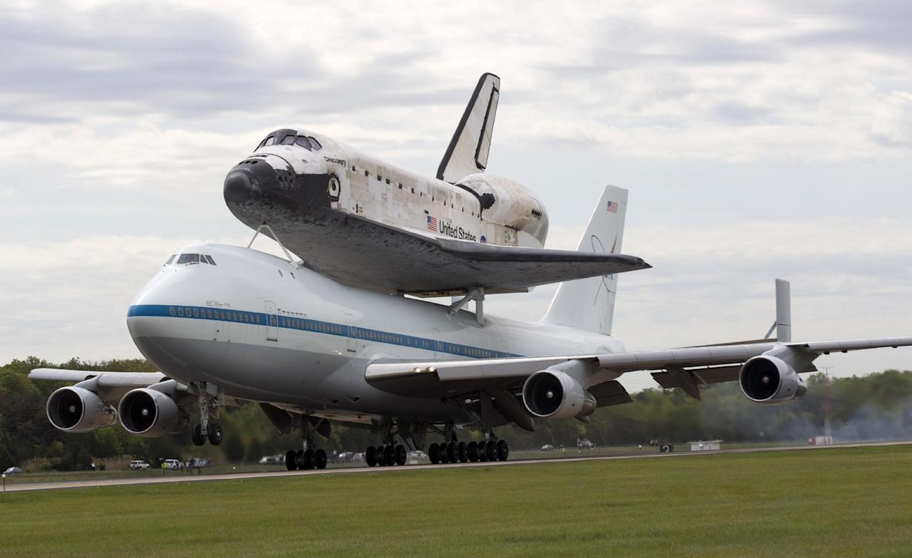 The space shuttle Discovery, sitting atop a 747 carrier aircraft, lands at Dulles International Airport in Chantilly, Va., Tuesday, April 17, 2012. Discovery, the longest-serving orbiter will be placed to its new home, the Smithsonian's National Air and Space Museum's Steven F. Udvar-Hazy Center in Chantilly, Va. (AP Photo/Manuel Balce Ceneta)