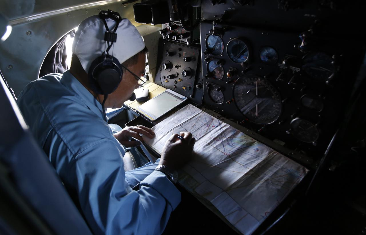 A military officer takes notes during a search and rescue mission, onboard an aircraft belonging to the Vietnamese airforce, off Vietnam's Tho Chu island