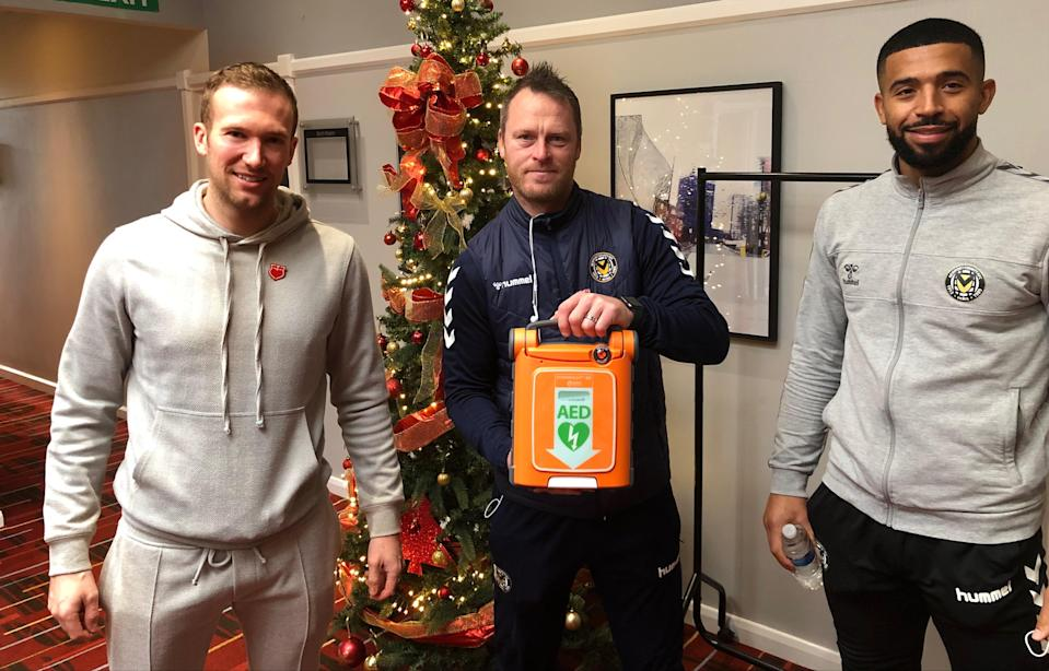 Charlie Edinburgh recently presented Newport manager Michael Flynn and captain Joss Labadie with an automated external defibrillator on behalf of the Justin Edinburgh 3 Foundation