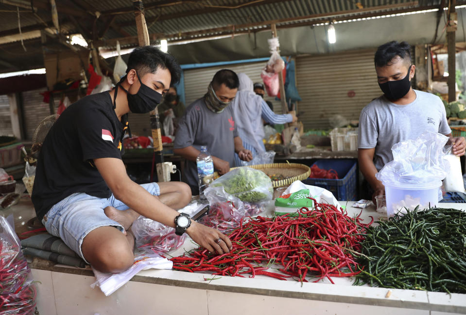 Vendors wearing protective mask as a precaution against the new coronavirus outbreak sort chili peppers at a market in Jakarta, Indonesia, Thursday, June 25, 2020. (AP Photo/Tatan Syuflana)