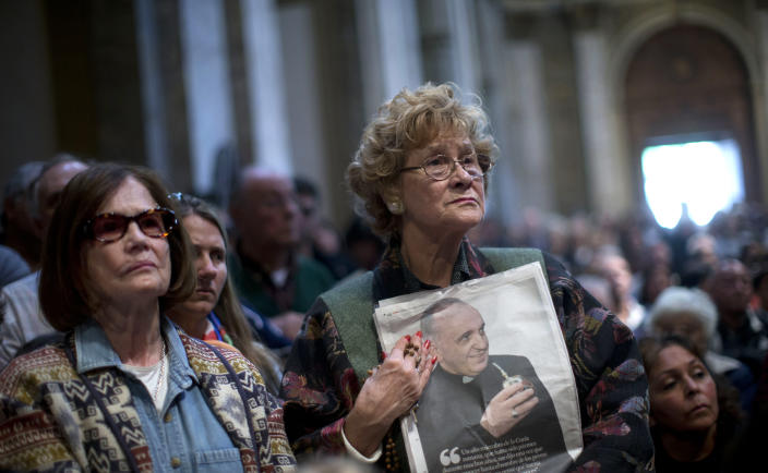 A worshiper holds a newspaper showing Pope Francis drinking mate during a Mass for the pope at the Metropolitan Cathedral in Buenos Aires, Argentina, Sunday, March 17, 2013. Argentine's former Cardinal Jorge Mario Bergoglio was chosen as leader of the Catholic Church on March 13, 2013. (AP Photo/Natacha Pisarenko)