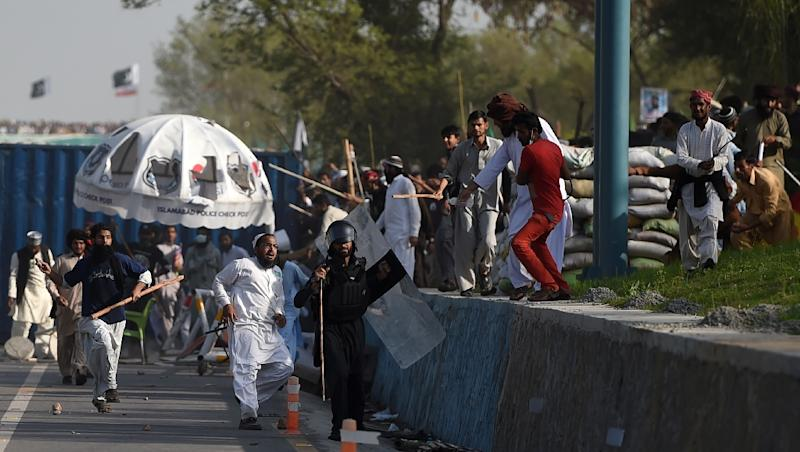 A Pakistani Frontier Constabulary official runs from supporters of executed Islamist Mumtaz Qadri during an anti-government rally in Islamabad on March 27, 2016 (AFP Photo/Farooq Naeem)