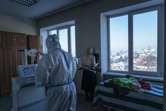 A medic wearing a special suit to protect against coronavirus, back to a camera prepares a patient with coronavirus for a lung X-ray at a hospital in Kolomyia, western Ukraine, Tuesday, Feb. 23, 2021. After several delays, Ukraine finally received 500,000 doses of the AstraZeneca vaccine marketed under the name CoviShield, the first shipment of Covid-19 vaccine doses. The country of 40 million is one of the last in the region to begin inoculating its population. (AP Photo/Evgeniy Maloletka)