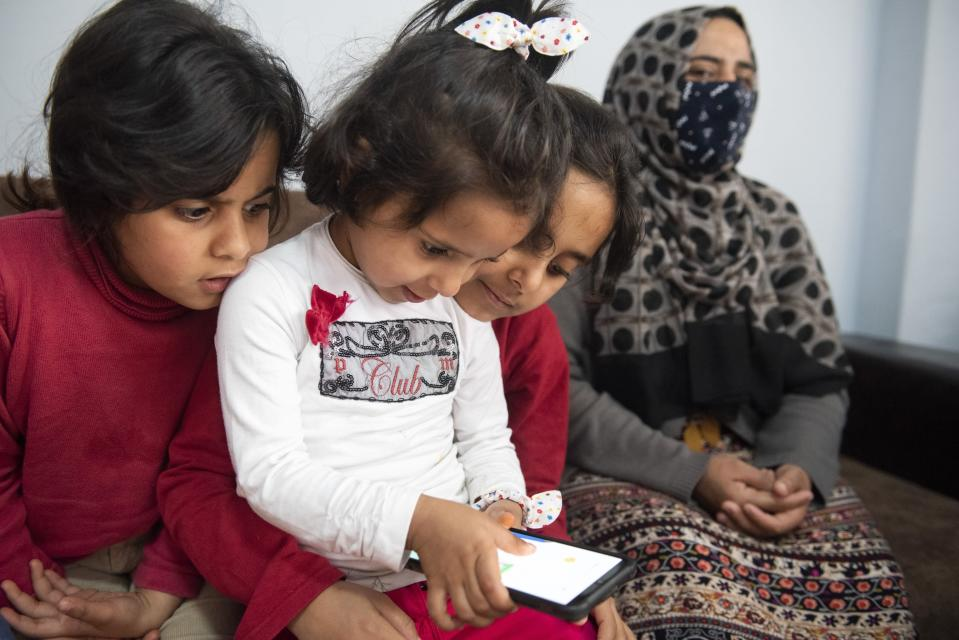Bayan, left, Safa, center, and Iman play with a cellphone as they sit next to their mother Kariman, 32 at their apartment in the northern city of Thessaloniki, Greece, Saturday, May 1, 2021. Sundered in the deadly chaos of an air raid, a Syrian family of seven has been reunited, against the odds, three years later at a refugee shelter in Greece's second city of Thessaloniki. (AP Photo/Giannis Papanikos)