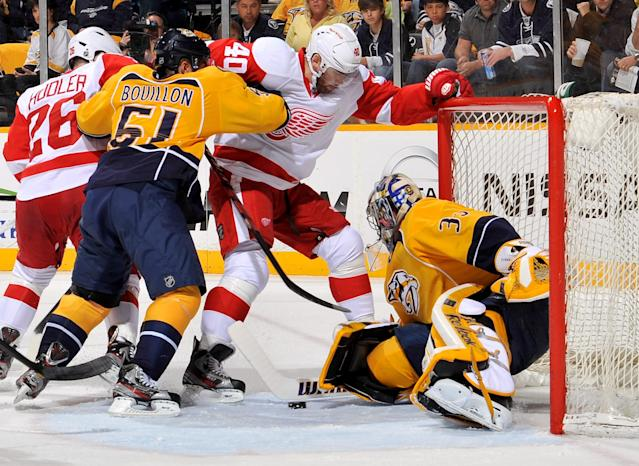 NASHVILLE, TN - APRIL 13: Henrik Zetterberg #40 of the Detroit Red Wings and Francis Bouillon of the Nashville Predators fight for the puck in front of goalie Pekka Rinne #35 in Game Two of the Western Conference Quarterfinals during the 2012 NHL Stanley Cup Playoffs at the Bridgestone Arena on April 13, 2012 in Nashville, Tennessee. (Photo by Frederick Breedon/Getty Images)