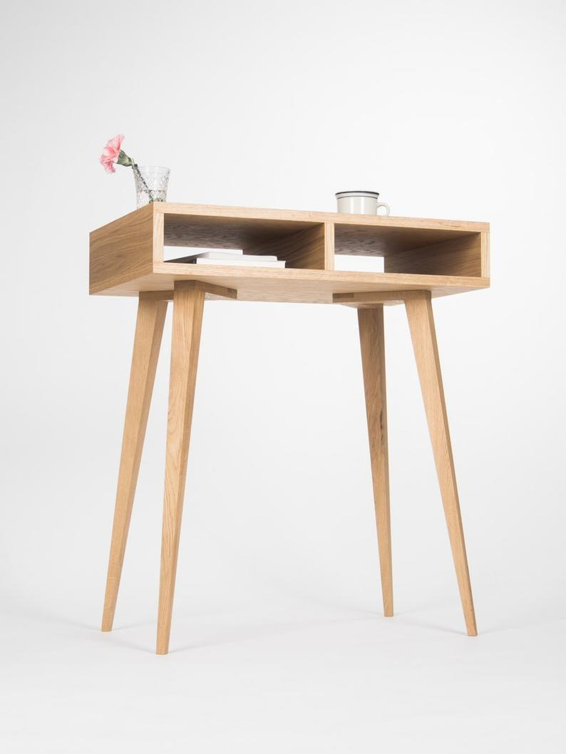 """<h3>ModWdwrk Small Oakwood Desk</h3><br>This small but sturdy desk fits comfortably in a living room or bedroom without taking up too much space, is crafted from smooth beautiful oakwood, and is easy to assemble (you'll need no more than 15 mins!) — with two built-in storage cubbies for stowing away your keyboard and other work supplies. <br><br><strong>MoWdwrk</strong> Small Oakwood Desk, $, available at <a href=""""https://go.skimresources.com/?id=30283X879131&url=https%3A%2F%2Fwww.etsy.com%2Flisting%2F400600673%2Fentryway-table-hallway-table-small-desk"""" rel=""""nofollow noopener"""" target=""""_blank"""" data-ylk=""""slk:Etsy"""" class=""""link rapid-noclick-resp"""">Etsy</a>"""