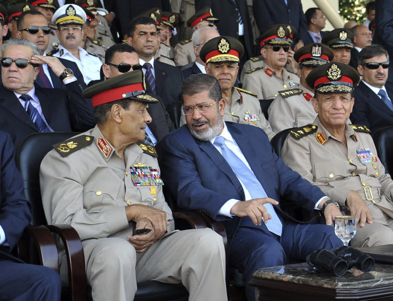 In this photo released by the office of the Egyptian Presidency, President Mohammed Morsi, second from right, talks with Field Marshal Hussein Tantawi, second left, as they attend a military graduation ceremony with Prime Minister Kamal el-Ganzouri, left, and Chief of Staff Sami Anan, right, in Cairo, Egypt, Tuesday, July 17, 2012. Egypt's President Mohammed Morsi hailed the Egyptian army and its commanders at a time the newly elected Islamist president and the military council, which took power after ouster of Hosni Mubarak last year, are in mid of power struggle. (AP Photo/Sheriff Abd El Minoem, Egyptian Presidency)