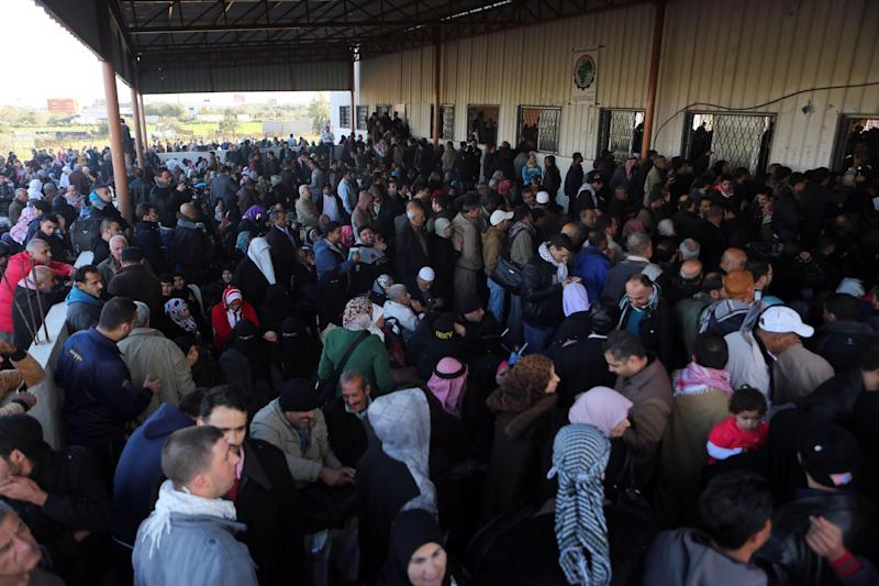 Palestinians await permission to enter Egypt as they gather inside the Rafah border crossing between Egypt and southern Gaza Strip on December 21, 2014 (AFP Photo/Said Khatib)
