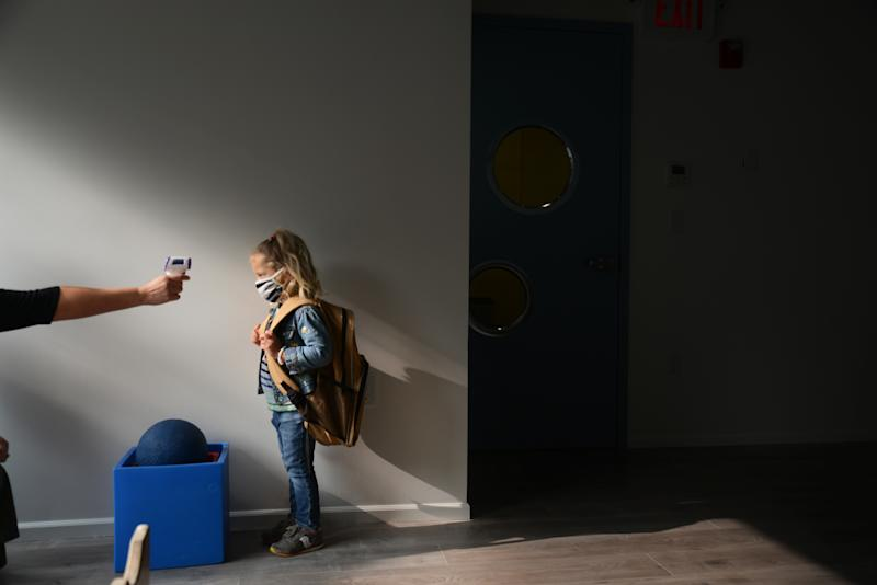 Students return for their first day of in-class schooling following the pandemic at New York City's Preschool of the Arts, having their temperatures checked before proceeding into the school, Tuesday, 15 September 2020. (Photo by B.A. Van Sise/NurPhoto via Getty Images)