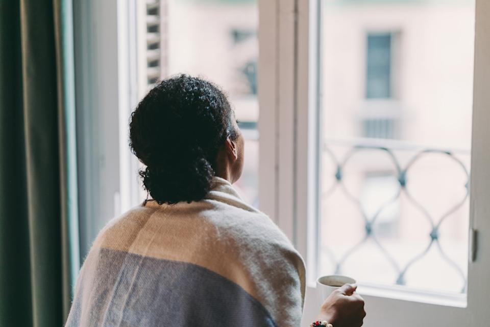 Woman in quarantine staying home, drinking coffee feeling depressed