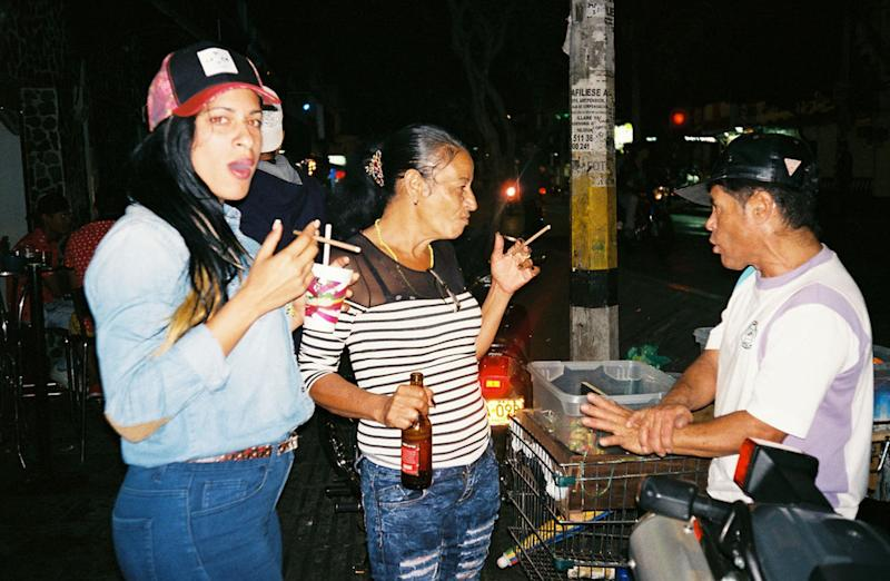May 2, 2016- Liset (left) and Marta with a street vendor in Medellín,after going out and partying with local coyotes. (Photo: Lisette Poole)