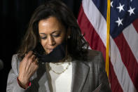 Democratic presidential candidate former Vice President Joe Biden's running mate Sen. Kamala Harris, D-Calif., removes her face mask as she prepares to speak at the Hotel DuPont in Wilmington, Del., Thursday, Aug. 13, 2020. (AP Photo/Carolyn Kaster)