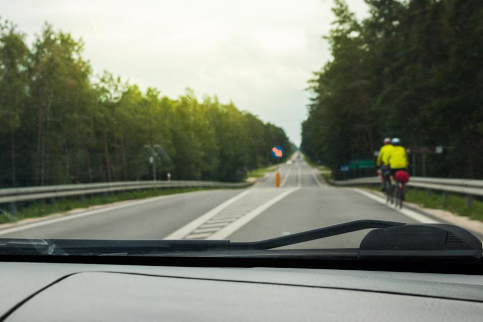 A car overtaking two cyclists. Source: Getty Images