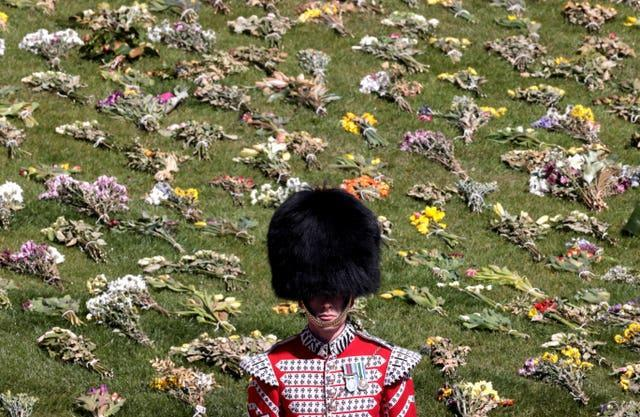 A guard stands in front of flowers laid out on the grass outside St George's Chapel, Windsor Castle, Berkshire, ahead of the funeral of the Duke of Edinburgh