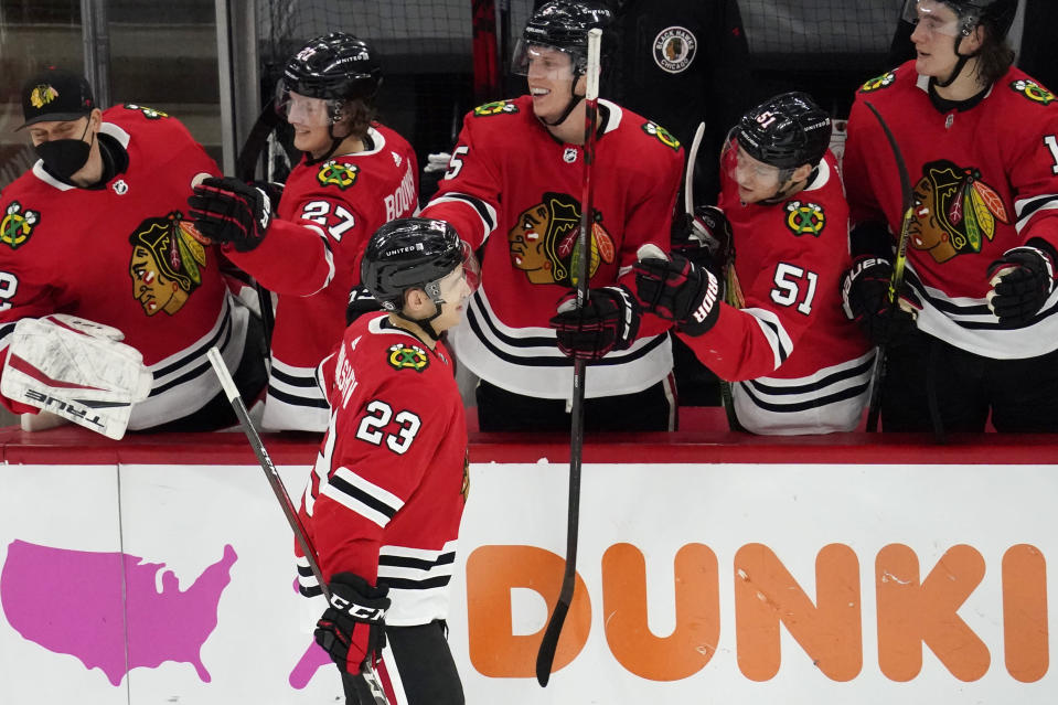 Chicago Blackhawks' Philipp Kurashev (23) celebrates with teammates after scoring a goal in a shootout of an NHL hockey game against the Tampa Bay Lightning in Chicago, Friday, March 5, 2021. (AP Photo/Nam Y. Huh)