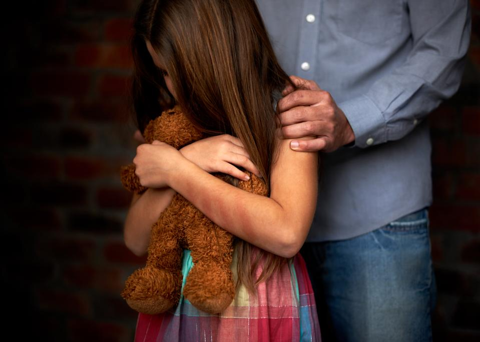 A girl hugging a stuffed toy with a man gripping her shoulders. (PHOTO: Getty Images)