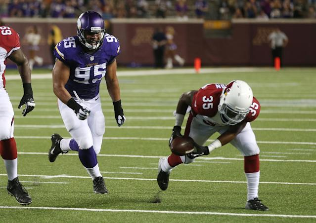 Arizona Cardinals running back Zach Bauman picks up a fumble and scores a touchdown in front of Minnesota Vikings defensive end Scott Crichton, left, during the second half of an NFL preseason football game, Saturday, Aug. 16, 2014, in Minneapolis. The Vikings won 30-28. (AP Photo/Jim Mone)