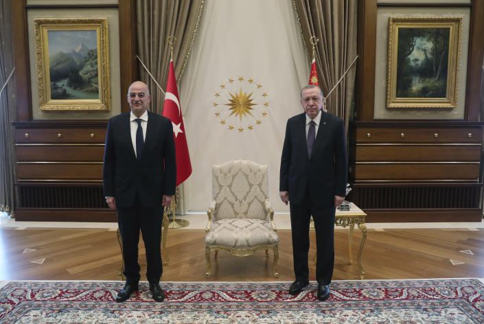 Turkey's President Recep Tayyip Erdogan, right, poses for photographs with Greek Foreign Minister Nikos Dendias, left, prior to their meeting in Ankara, Turkey, Thursday, April 15, 2021. Dendias travelled to Ankara for talks on the two NATO allies' fraught relationship, following a slight easing of tensions between the neighbors. In an indication of the meeting's importance, Dendias was invited to meet Erdogan as well as his counterpart, Mevlut Cavusoglu. (Turkish Presidency via AP)