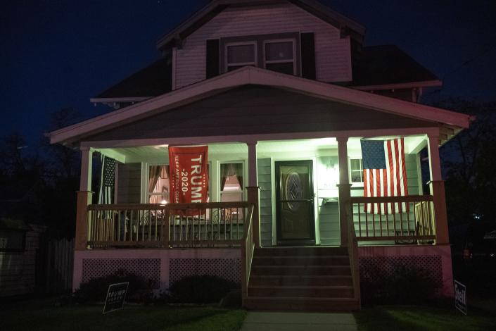 A Trump flag and an American flag hang on the front porch of a home in Kenosha, Wis., Friday, Oct. 30, 2020. The trouble in Kenosha began on Aug. 23 when a Kenosha police officer, responding to a call about a domestic dispute, was caught on video shooting Jacob Blake repeatedly in the back at close range. Blake, a Black man, survived but is partially paralyzed. The August shootings have spurred a spike in political involvement in Kenosha, with the formation of activism and waves of new voters signing up. (AP Photo/Wong Maye-E)
