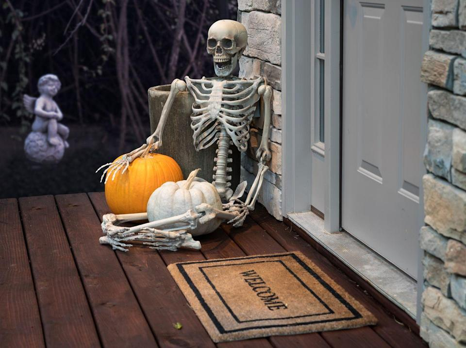 """<p>Is it even Halloween if a skeleton is not part of your decor? Place one right on the floor next to your door, and wait for the screams from neighbors and trick-or-treaters. </p><p><a class=""""link rapid-noclick-resp"""" href=""""https://go.redirectingat.com?id=74968X1596630&url=https%3A%2F%2Fwww.orientaltrading.com%2Fhanging-skeleton-halloween-d-cor-a2-13687726.fltr&sref=https%3A%2F%2Fwww.goodhousekeeping.com%2Fholidays%2Fhalloween-ideas%2Fg32948621%2Fhalloween-door-decorations%2F"""" rel=""""nofollow noopener"""" target=""""_blank"""" data-ylk=""""slk:SHOP SKELETON DECOR"""">SHOP SKELETON DECOR</a></p>"""