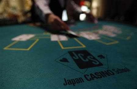 A logo of Japan casino school is seen as a dealer puts cards on a mock black jack casino table during a photo opportunity at an international tourism promotion symposium in Tokyo