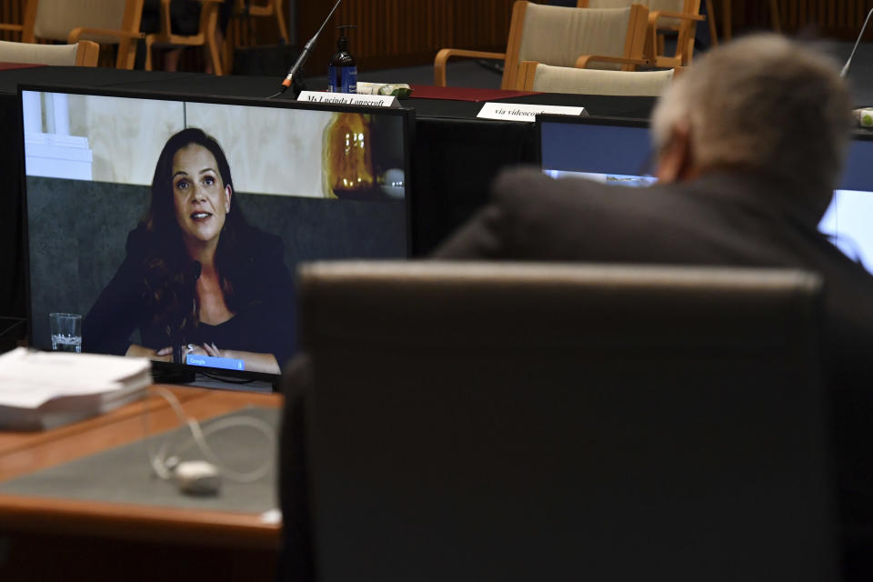 Mel Silva, left, the managing director of Google Australia and New Zealand, appears via a video link during a Senate inquiry into a mandatory code of conduct proposed by the government at Parliament House in Canberra, Friday, Jan. 22, 2021. Google on Friday threatened to make its search engine unavailable in Australia if the government went ahead with plans to make tech giants pay for news content. (Mick Tsikas/AAP Image via AP)