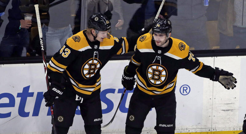 Boston Bruins left wing Jake DeBrusk (74) celebrates his goal with teammates Danton Heinen (43) and David Krejci (46) in the third period of an NHL hockey game against the Calgary Flames, Thursday, Jan. 3, 2019, in Boston. The Bruins won 6-4. (AP Photo/Elise Amendola)