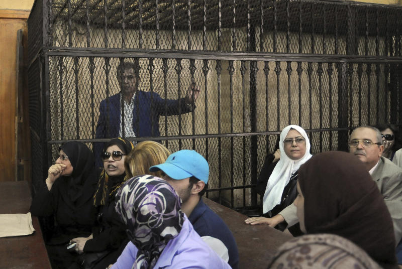 """Tawfiq Okasha, a popular Egyptian TV presenter accused of inciting the killing of the country's new president on air, stands in the defendants cage at the opening of his trial, in Cairo, Egypt, Saturday Sept. 1, 2012. Egypt's state news agency said the prosecutor accused Okasha of using his TV program in July and August to incite the killing of President Mohammed Morsi, and of insulting him by calling him an """"illegitimate leader and a liar."""" (AP Photo/Mohammed Assad)"""