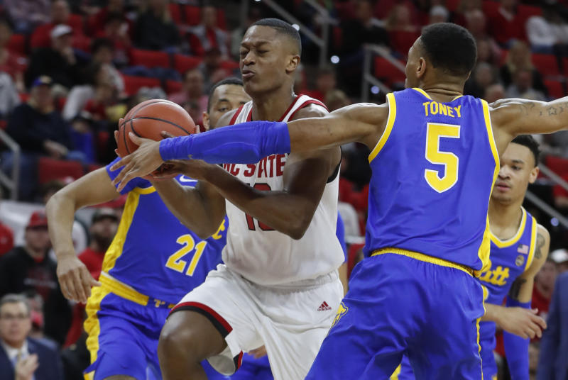 North Carolina State's C.J. Bryce (13) drives past Pittsburgh's Au'Diese Toney (5) during the first half of an NCAA college basketball game at PNC Arena in Raleigh, N.C., Saturday, Feb. 29, 2020. (Ethan Hyman/The News & Observer via AP)