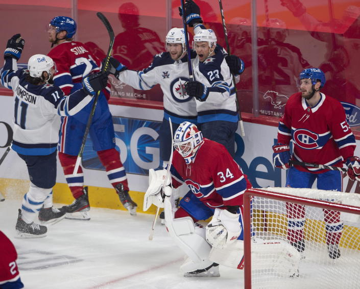 Winnipeg Jets center Trevor Lewis (23) celebrates his goal with teammates Jansen Harkins (12) and Nate Thompson (11) as Montreal Canadiens goaltender Jake Allen (34), Eric Staal (12) and Victor Mete (53) look on during the first period of an NHL hockey game, Thursday, April 8, 2021 in Montreal. (Ryan Remiorz/The Canadian Press via AP)