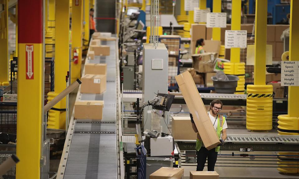 Workers pack and ship customer orders at the Amazon fulfillment center Romeoville, Illinois on 1 August 2017. (Credit/The Guardian)
