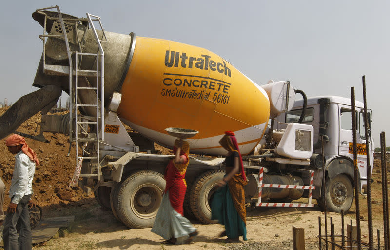 Workers walk in front of an UltraTech concrete mixture truck at the construction site of a commercial complex on the outskirts of Ahmedabad