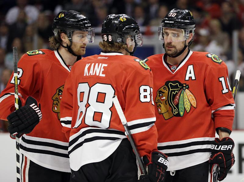 Chicago Blackhawks' Patrick Sharp (10) talks with teammates Duncan Keith (2) and Patrick Kane (88) during the second period of Game 1 of an NHL hockey playoffs Western Conference semifinal against the Detroit Red Wings in Chicago, Wednesday, May 15, 2013. (AP Photo/Nam Y. Huh)