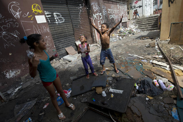 Children play near abandoned buildings, in an area recently occupied by squatters, in Rio de Janeiro, Brazil, Wednesday, April 9, 2014. Thousands of people have laid claim to a compound of abandoned office buildings owned by the private telecommunications company Oi, and named their settlement after the state-owned telecommunications Telerj. Authorities are negotiating with squatters to leave peacefully from the area they have occupied for more than a week. (AP Photo/Silvia Izquierdo)