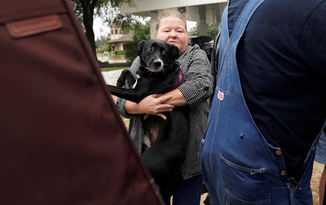 <p>A woman carries her dog into a collector's vintage military truck to evacuate from flood waters from Hurricane Harvey in Dickinson, Texas Aug. 27, 2017. (Photo: Rick Wilking/Reuters) </p>