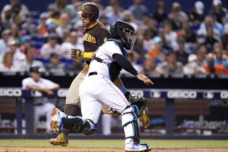 San Diego Padres' Tommy Pham, left, scores past Miami Marlins catcher Jorge Alfaro on a single hit by Jurickson Profar during the fourth inning of a baseball game, Thursday, July 22, 2021, in Miami. (AP Photo/Lynne Sladky)
