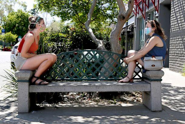 PHOTO: In this April 27, 2020, file photo, Catie Fee, left, and Vivi Kirsh, practice social distancing and wear face masks as they sit in downtown Davis, Calif. (Rich Pedroncelli/AP, FILE)