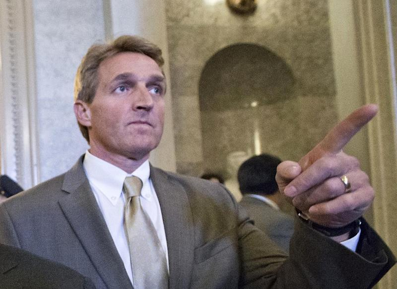 FILE - In this Feb. 28, 2013 file photo, Sen. Jeff Flake, R-Ariz. gestures as he leaves the Senate chamber on Capitol Hill in Washington. Authorities are investigating two suspicious letters that were sent to the Phoenix office of  Flake. Emergency crews in hazardous materials gear were seen outside the building.  (AP Photo/J. Scott Applewhite, File)