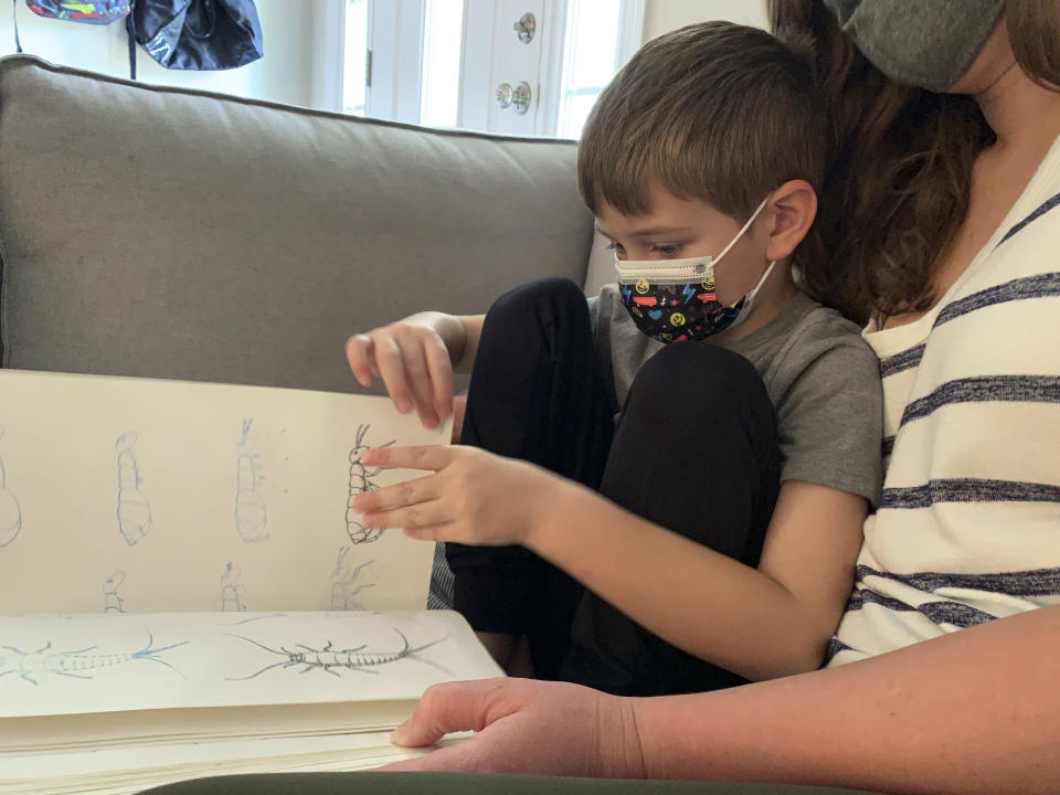 Five-year-old Berkeley Goss reads through his favorite book about bugs inside his Monroe, N.C. home. His parents, Jeff and Emily Goss chose to pull him out of the Union County School District where he had attended the first week of in-person kindergarten fearing the lack of mask requirements would lead to a COVID-19 infection for Berkeley or his at-risk family members. (AP Photo/Sarah Blake Morgan)