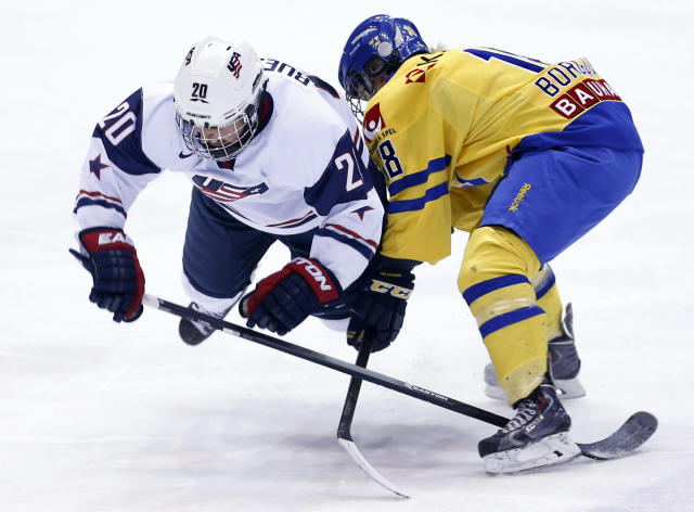 United States' Kate Buesser (20) is tripped by Sweden's Anna Borgqvist (18) during the second period of a Four Nations Cup women's third-place hockey game on Saturday, Nov. 9, 2013, in Lake Placid, N.Y. (AP Photo/Mike Groll)