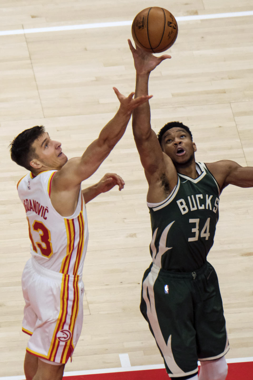 Milwaukee Bucks forward Giannis Antetokounmpo (34) knocks the rebound away from Atlanta Hawks guard Bogdan Bogdanovic (13) during the first half of an NBA basketball game on Sunday, April 25, 2021, in Atlanta. (AP Photo/Ben Gray)